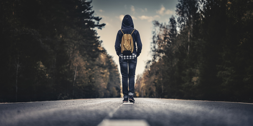 person-with-backpack-walking-in-the-middle-of-the-road